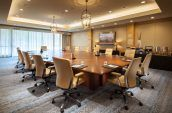 a meeting room with large square table office chairs large window and painting on the wall