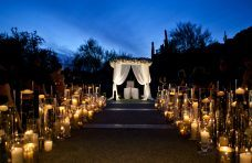 outdoor wedding at dusk with two lines of candles down the path to the altar