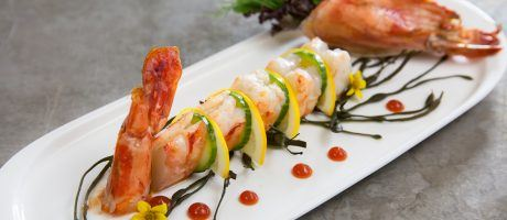 a beautifully plated cooked shrimp cut into slices and separated with slices of lemon and cucumber