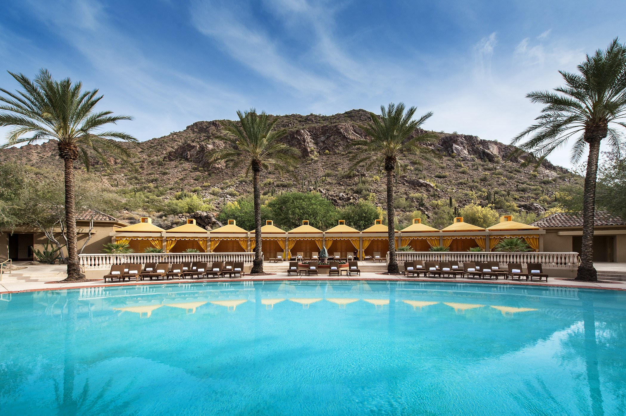 large circular pool at luxury hotel surrounded by palm trees and yellow cabanas