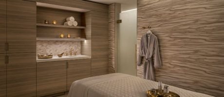 a treatment room featuring a therapy bed with wood style closet and robe hanging on the wall