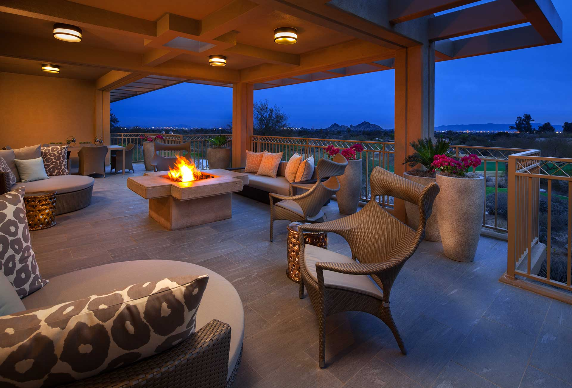 outdoor patio covered by roof with chairs and fire pit